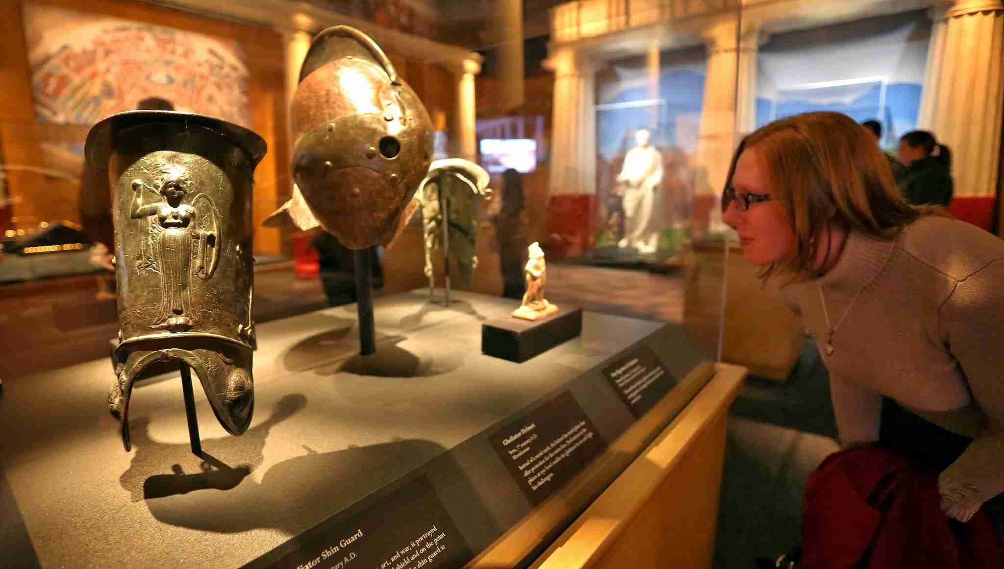 Museum visitor examining gold artifact from Pompeii: The Exibition